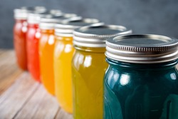 A view of a row of glass mason jars with a rainbow color scheme.