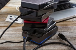 A view of a several external hard drives stacked together in front of a laptop computer on a wooden surface.