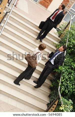 A view of a several people belonging to a business team, standing on the steps of an office building having informal conversation as they leave following an important meeting.