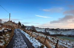 a view of a snow covered narrow country lane with a row of stone houses surrounded by fields at hurst lane in hebden bridge surrounded by west yorkshire pennine landscape
