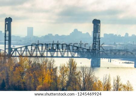 A view of a steel bridge and the Portland Oregon hazy skyline.