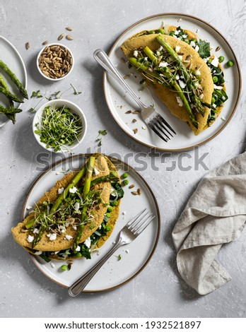 A view of a table with delicious, freshly made vegan crepes ready to be eaten. Made of nutirious chickpea flour, filled with spinach, peas and vegan cheese, topped with grilled asparagus and seeds