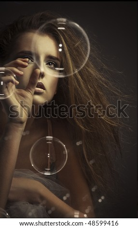 A view of a teenage girl reaching out as if to touch a large bubble floating in front of her.
