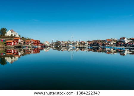 A view of a the  harbor at Grundsund Bohuslän in the morning. With boat houses, blue water and sky. #1384222349