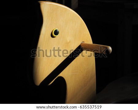 A view of a wooden baby horse lit by an evening sun in a dark room #635537519