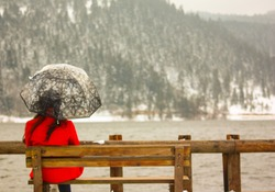 A view of alone and sad girl in red coat and black hair with umbrella sitting on a wooden bench  against the forest by the lake.