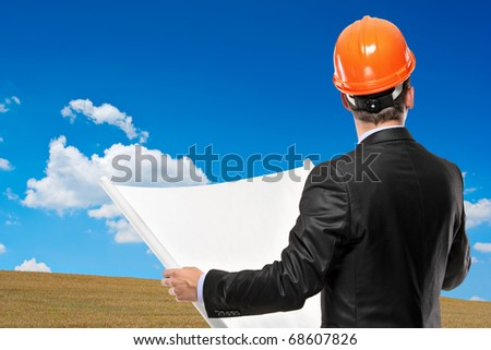 A view of an architect holding a blueprint with a green meadow in the background