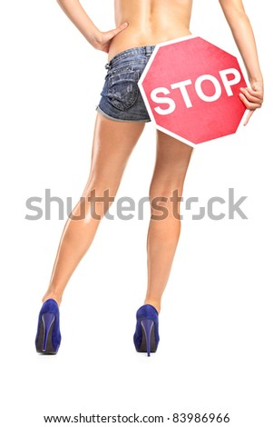 A view of an attractive woman holding a traffic sign stop over her buttock isolated on white background