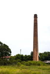 A view of an old brick chimney that is no longer in use standing tall among the grasses and trees in a rural area of Thailand.
