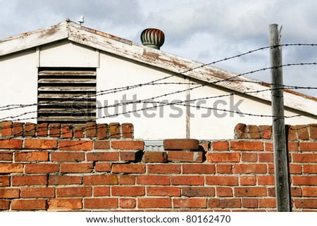 A view of  barbed wire attached to a timber post along the top of a red brick wall - stock photo