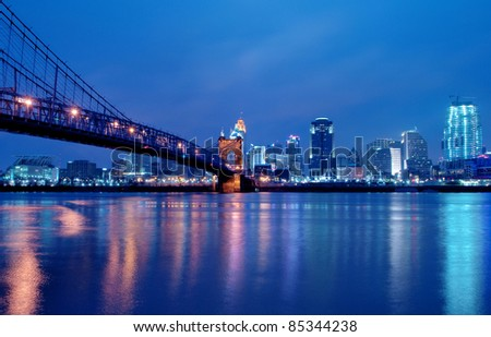 A view of Cincinnati, Ohio?s skyline cityscape overlooking the Ohio River at night.