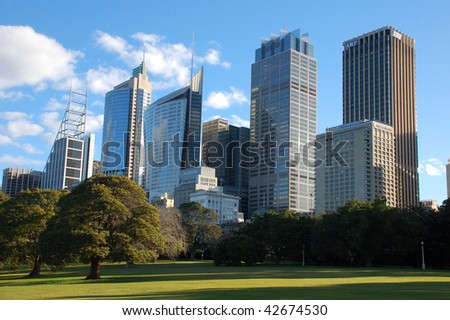 A view of city skyscrapers taken from Royal Botanic Gardens with lawn in foreground