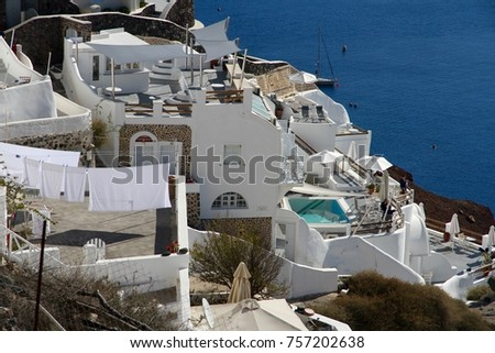 A view of colorful cubiform buildings on Santorini Island in Greece clinging to the cliff over the Aegean Sea.  #757202638