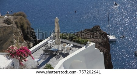 A view of colorful cubiform buildings on Santorini Island in Greece clinging to the cliff over the Aegean Sea.  #757202641