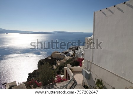 A view of colorful cubiform buildings on Santorini Island in Greece clinging to the cliff over the Aegean Sea.  #757202647