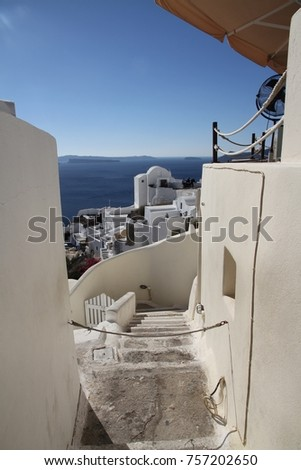 A view of colorful cubiform buildings on Santorini Island in Greece clinging to the cliff over the Aegean Sea.  #757202650