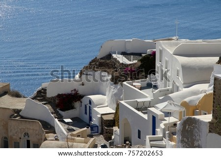 A view of colorful cubiform buildings on Santorini Island in Greece clinging to the cliff over the Aegean Sea.  #757202653