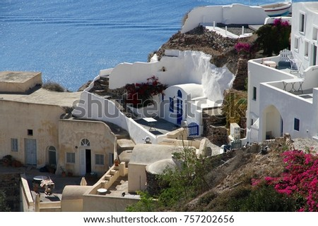 A view of colorful cubiform buildings on Santorini Island in Greece clinging to the cliff over the Aegean Sea.  #757202656