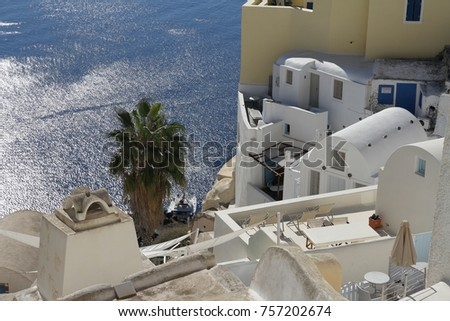 A view of colorful cubiform buildings on Santorini Island in Greece clinging to the cliff over the Aegean Sea.  #757202674