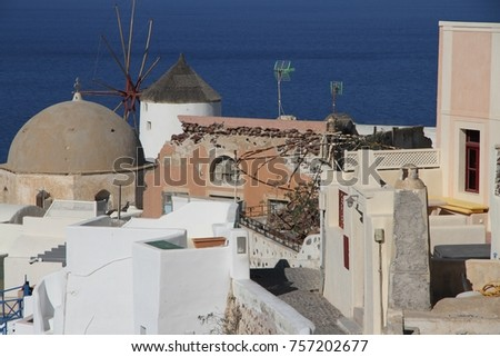 A view of colorful cubiform buildings on Santorini Island in Greece clinging to the cliff over the Aegean Sea.  #757202677