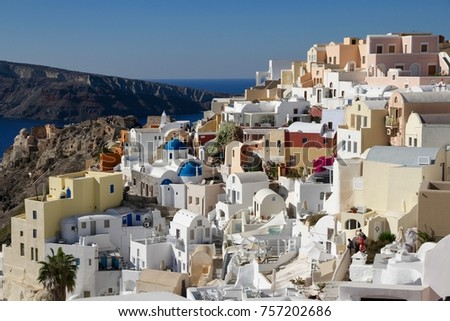 A view of colorful cubiform buildings on Santorini Island in Greece clinging to the cliff over the Aegean Sea.  #757202686