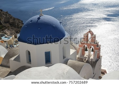 A view of colorful cubiform buildings on Santorini Island in Greece clinging to the cliff over the Aegean Sea.  #757202689