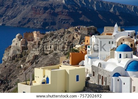 A view of colorful cubiform buildings on Santorini Island in Greece clinging to the cliff over the Aegean Sea.  #757202692