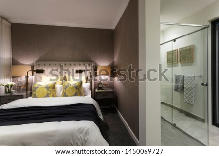 A view of cozy bedroom with sophisticated interior design and matching furnishing attached to a bathroom with walk-in shower made of glass. #1450069727
