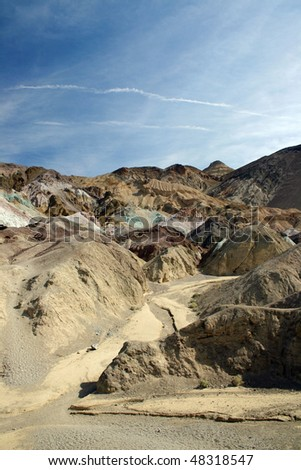 A view of Death Valley shows the colorful rock mountain with aircraft trails in the blue sky.