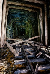 A view of derelict, narrow-gauge rail / tracks of the East Broad Railroad inside a long abandoned and collapsing timber-lined tunnel in Pennsylvania.