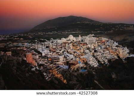 A view of Fira, the main town on the Greek holiday island of Santorini, as the sun sets painting the sky a delicate pink.