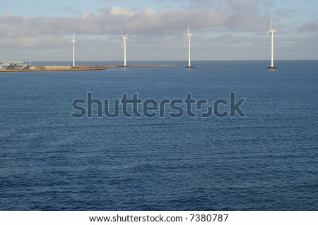 A view of four tall wind-powered electricity generators built just offshore in Frederikshavn, Denmark. - stock photo
