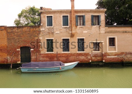 A view of historical buildings and canals of toruistic city Venice, Italy. Boats on the river, canal in the city. Great architecture of Italy. Retro, vintage, old style architecture of the country.
