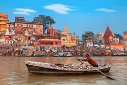A view of  holy ghats of Varanasi with a boatman sailing