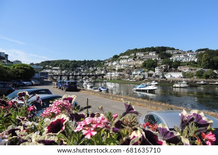 A view of Looe, with the bridge across the river leading to the sea, and boats moored safely at low tide