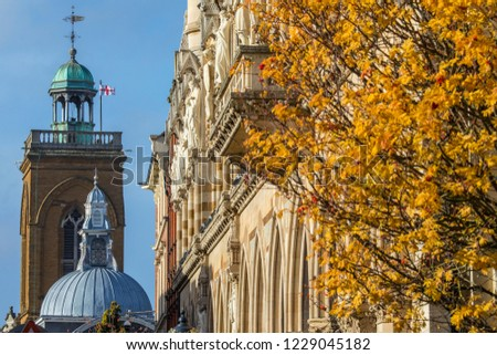 A view of looking across the facade of Northampton Guildhall and the tower of All Saints Church in the town of Northampton, UK.