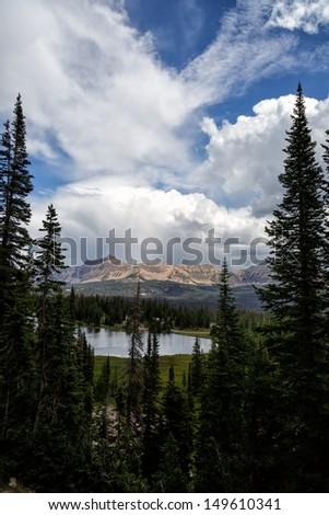 A view of Moose Horn Lake with Hayden Peak in the distance under thunderclouds and blue sky between storms/ Moose Horn Lake Through the Pines