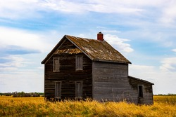 A view of old abandoned farm houses that were left to be reclaimed by nature. These structures are in a state of disrepair and are starting to collapse as they were forgotten on the prairies.
