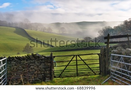 A view of rolling English Countryside near Staveley, Cumbria. Mist i the distance, and a gate and dry-stone wall in the foreground