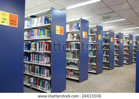 A view of rows of bookshelves and a study area inside a library.