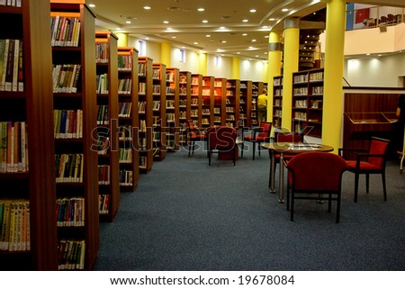 A view of rows of bookshelves and a study area inside a modern library.