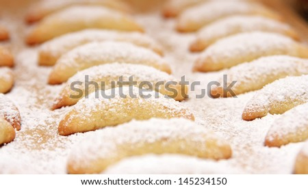 A view of rows of freshly baked cookies covered with white powdered sugar.