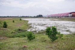 A view of sediment basin at construction site during monsoon season. Image contains certain grain or noise and soft focus.