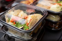A view of several entrees prepared inside to-go plastic containers, ready for take out orders, in a restaurant setting.