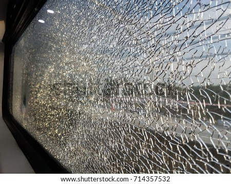 A view of shattered window glass panel on board the commuter train. A selective focus view.  Stok fotoğraf ©
