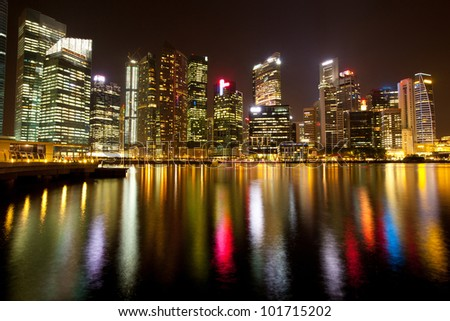A view of Singapore business district in the night time with water reflections.