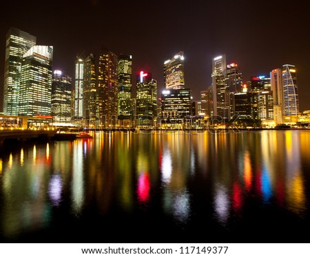 A view of Singapore business district Marina Bay, in the night time, with water reflections.