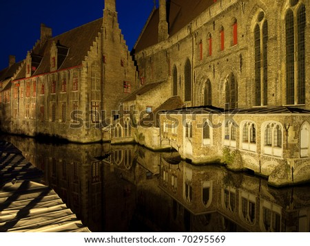 A view of St. John's Hospital in Bruges, Belgium as seen from across the canal at night.