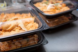 A view of stacks of entrees prepared inside to-go plastic containers, ready for take out orders, in a restaurant setting.