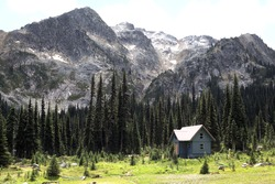 A view of the Brian Waddington hut, a sanctuary for hikers who explore this stunning wild and remote Canadian natural landscape of alpine mountains, green conifers, and blue lakes